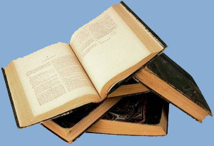 Open antiquarian book on stack of books