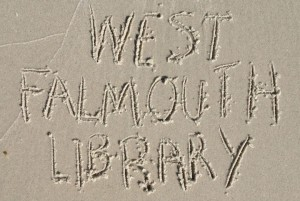 West Falmouth Library written in the sand at Chappaquoit Beach